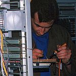 Kevin McMahon installing cabling for telephone exchange equipment.